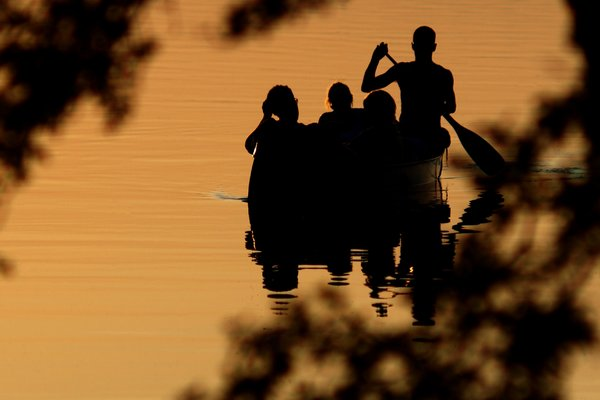 Canoeing: A family sailing a canoe in the sunset.