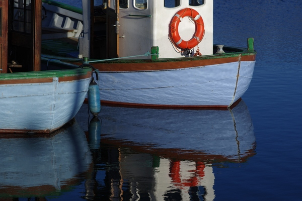 Fishing boats: Stern of two fishing boats with reflections