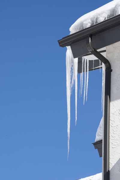 Icicles hanging from roof: Icicles hanging from corner of house roof  gutters on a cold winter day