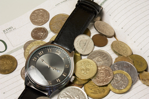 Time is Money!: A wrist watch on an agenda surounded by coins from all around the world.