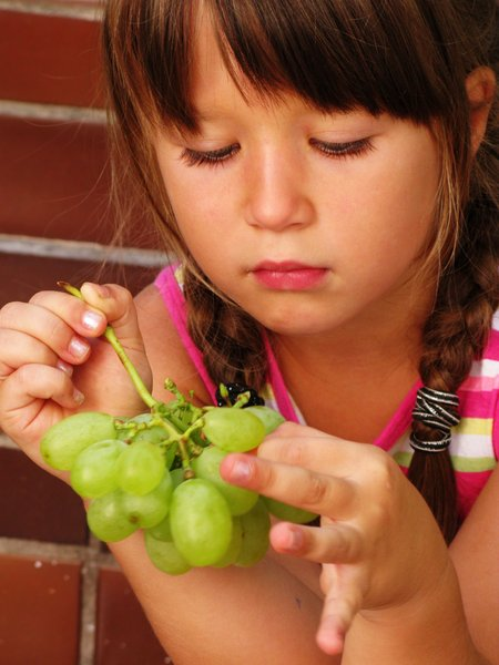 girl eating grapes: none