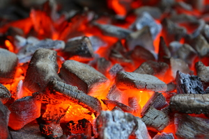 Searing hot charcoal: Glowing charcoal in a barbecue grill