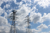 transmission towers: two giant transmission towers stand in front of blue sky.
