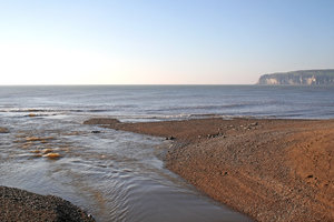 River mouth: The mouth of a river where it meets the sea near Lyme Regis, England.