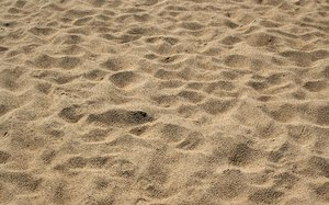 Beach sand with footprints: Coarse sand with lots of footprints on a beach in Kent, England.