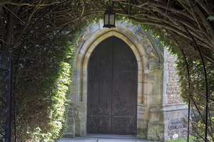 Church door: A church door and yew tree (Taxus) pergola in West Sussex, England