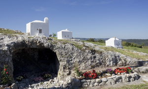 Gravestones like tiny houses: Gravestones resembling tiny houses and, underneath, a small grotto in a rural churchyard in Puglia, southern Italy.