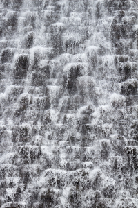 Dam cascade: Water cascading over aerator blocks on a dam wall in Wales.