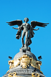 Winged female statue: A winged female statue on the dome of a tower in Madrid, Spain.