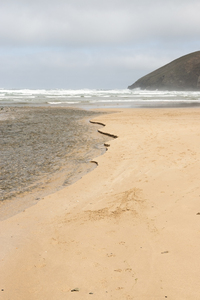 River reaching the sea: River mouth at a beach in north Cornwall, England.