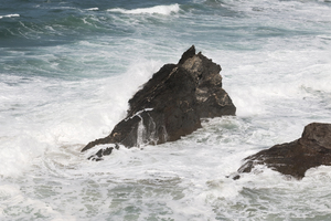 Rocks and crashing waves: Rocks amid violent waves on the coast of Cornwall, England.