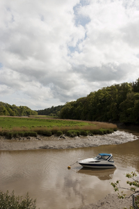 River bend with boat: A boat on a bend in a river in Cornwall, England.