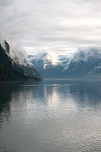 Moody fjord: A fjord in Norway with sunlight breaking through very low cloud early in the morning.