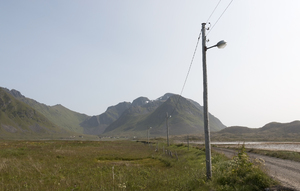 Landscape with telegraph poles: Telegraph poles with lights beside a causeway road across treacherous ground on the Lofoten Islands, Norway.