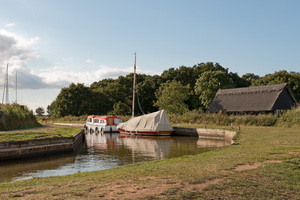 Canal scene: Boats moored on a mill canal on the Norfolk Broads, England.