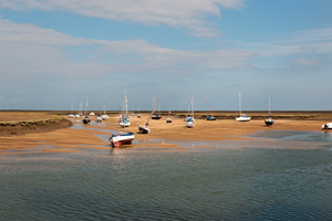 Boats in a creek: Boats moored in a creek at low tide at Wells-next-the-Sea, Norfolk, England.