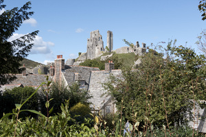 Village and castle: Cottages and ruins of Corfe Castle, Dorset, England. Photograph taken from a public footpath.