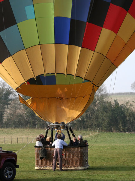 Hot Air Balloon: Inflating a hot air balloon using gas burners in early evening in England in spring.