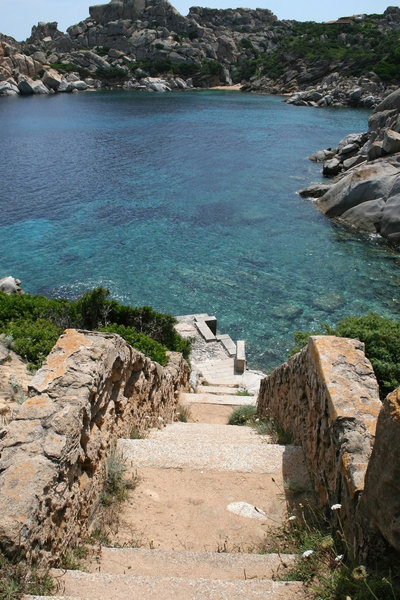 Steps: Steps to a quay beside a coastal inlet in Sardinia.