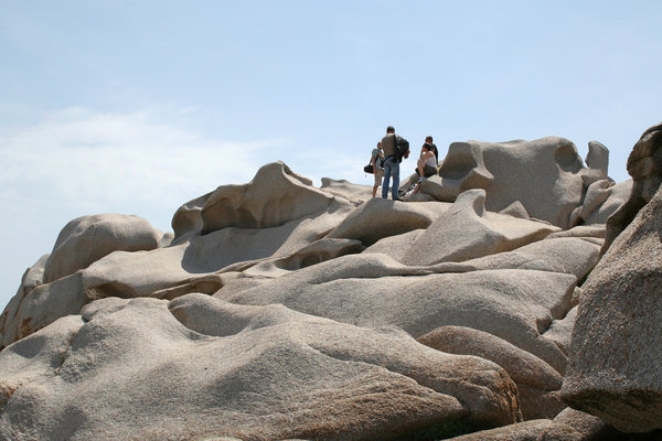 Tourists on sculpted rock: Tourists on a rock formation naturally sculpted by the wind in Sardinia.