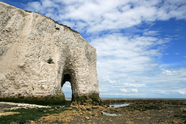 Cliff arch: An arch in a chalk cliff at low tide in Kent, England.
