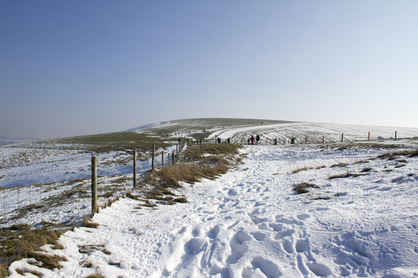 Walkers in the snow: Walkers in snow on the top of the South Downs, West Sussex, England, in February.