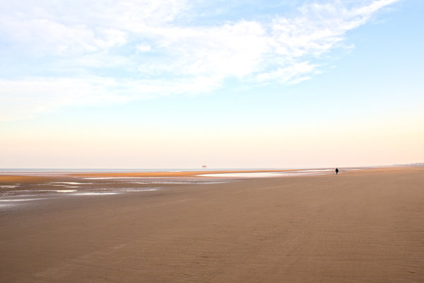 Lone walker on beach: A lone walker on the beach at Blackpool, northern England, at dawn.