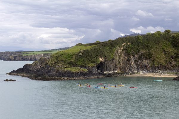 Sea canoeists: Canoeists following the coastline of Pembrokeshire, Wales.