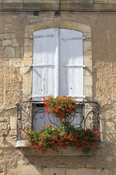 Window shutters and balcony: Window shutters and balcony on an old house in the Dordogne, France.