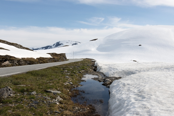 Snow road: A road through snowy mountains on a high plateau in Norway in July, with the beginnings of snow melt.
