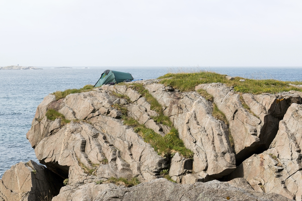 Extreme camping: Camping on a cracked cliff on the Lofoten Islands, Norway.