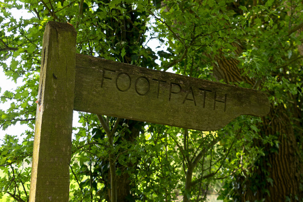 Old footpath sign: An old wooden footpath sign in Hampshire, England, in spring.
