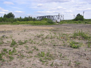 Scorched ground: Unused dead grounds near the railway. A railway bridge. In the distance there is a railway bridge.