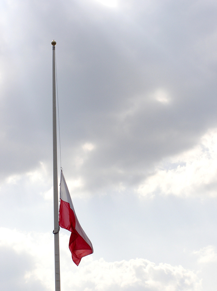 Polish Flag at Half Staff: Lowered flag and the clouds.