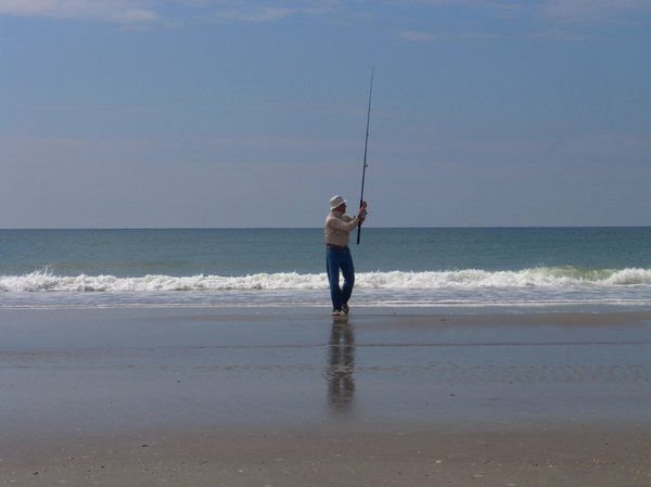 Surf Fishing: Man Surf fishing from the beach into the Atlantic Ocean. Summer