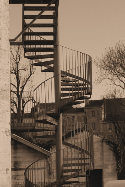 Curving Up: close shot of an outside spiral staircase at a disused factory.