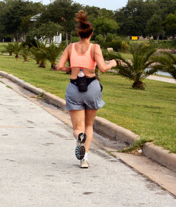 Jogger: cell phone and water bottle strapped to her.