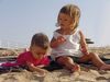 Dont eat the sand: Telling her sister not to eat the sand