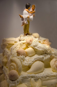 Beach Wedding Cake: Fondant wedding cake with bridal couple cake topper. Decorated with seashells. Notice the groom has his pants rolled up for the beach