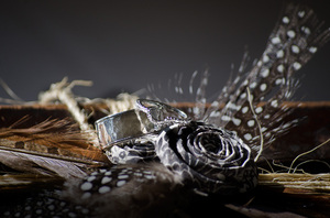 Wedding rings, feathers and pa: Wedding rings placed on paper roses and feathers