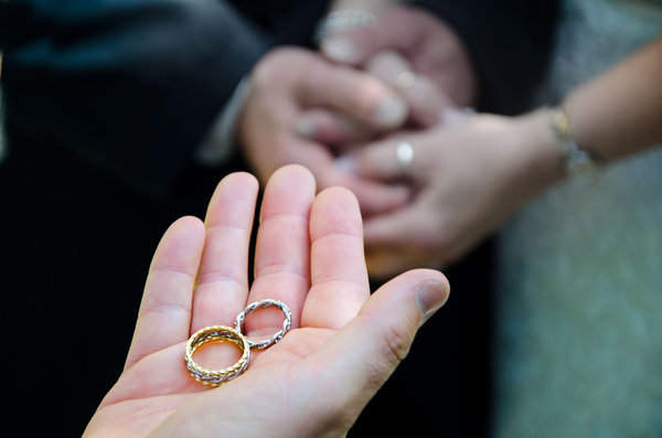 Wedding Rings: Wedding rings in priests hands with marriage couple hands in background