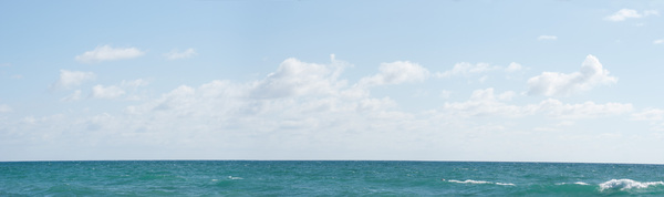 Generic Tropical Seascape: Fairly featureless seascape of tropical water, with midday cloudscape