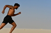 Runner on the sand in desert: Young adult man, is running on the sand hill in desert area and he is enjoying the sand and sunlight. His slim body suggests that he is a fitness model working out daily to maintain a healthy life style and healthy living habits.