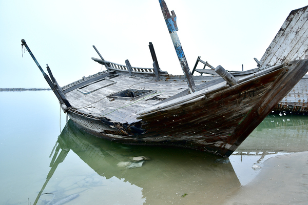 sunken ship ashore: Sunken old ship washed out on the shore bu the sea waves. Old ship wreck is now on the coast line ashore and all rusted metals and wrecked ship parts are there for everyone to see and photograph.