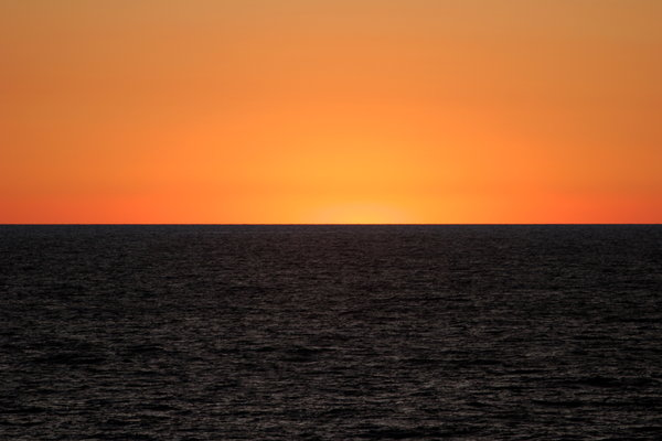 Black and Gold: Just after sunset at sea with clear horizon