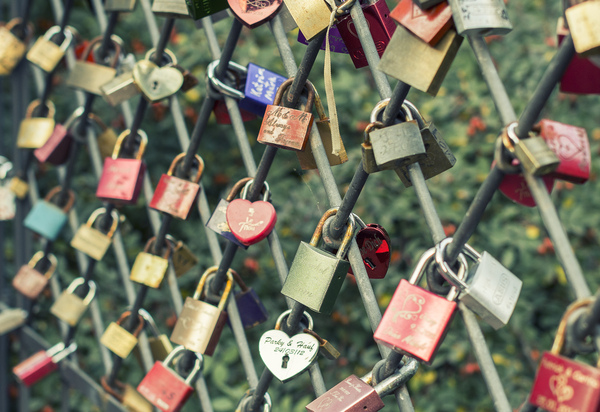 Love padlocks: Love padlocks locked to a fence with inscribed sweethearts' names