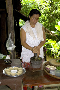 Thai cooking: Thai woman pounding the ingredients to make a curry paste