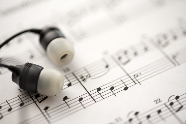 listening to music: a sheet of musical notes and some ear-bud headphones
