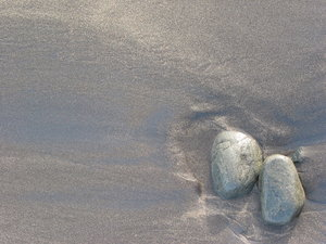 wet stone and sand 3: wet stones on sand series. Captured on Maspalomas beach, Gran Canaria, Spain. Sand with different colour and density results in these great patterns when waves reach objects on the beach.