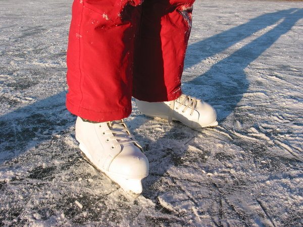 skates on ice: girls skates on lake ice.